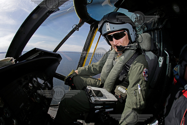 Pilot Bjørn Bottolfsen in the cockpit.  Crew from Norwegian Air Force 330 squadron, flying Westland Sea King helicopter. The core mission of the squadron is SAR (search and rescue), but they also fly HEMS (Helicopter Emergency Medical Service), complementing the civilian air ambulance service.<br /> This crew fly out of Rygge Air Station, Norway.
