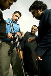 UK pilgrims Ali Hasham, Mohammed Ramzanali and Nadeem Abbas check the hotel Babylon's security's Kalashnikov..Baghdad, 29.02.04