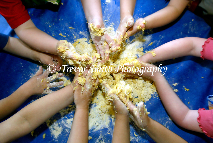 A group of children use their hands to make Pasta dough during a school lesson.