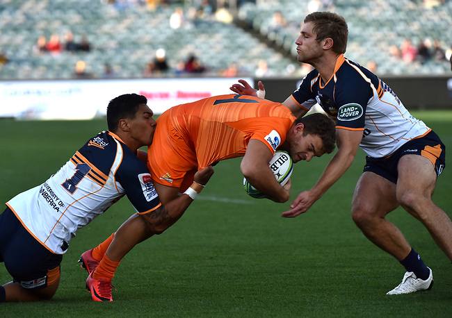 Jaguares player Emiliano Boffelli (C) is tackled by Brumbies players Chance Peni (L) and Kyle Godwin  (R) during the Super Rugby match between the ACT Brumbies and the Argentinian Jaguares at Canberra on April 22, 2018. AFP PHOTO / MARK GRAHAM --- IMAGE RESTRICTED TO EDITORIAL USE - STRICTLY NO COMMERCIAL USE --<br /> Resend with correct caption