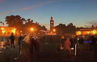 Evening view of entrance to Djemma el Fna square and marketplace, Medina, Marrakech, Morocco. The minaret of the Koutoubia mosque can be seen in the background. Picture by Manuel Cohen