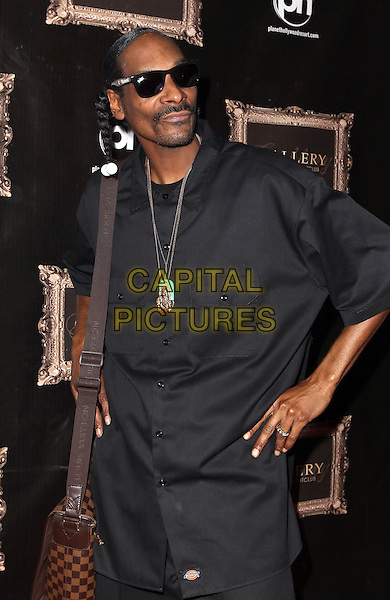 Snoop Dogg (Calvin Cordozar Broadus, Jr.) .Snoop walks the red carpet at Gallery Nightclub inside Planet Hollywood Hotel and Casino, Las Vegas, Nevada, USA..November 26th, 2011.half length black shirt braid plait pigtails sunglasses shades  brown bag satchel necklace hands on hips .CAP/ADM/MJT.© MJT/AdMedia/Capital Pictures.