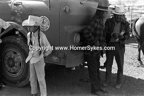 A young native American Indian with long pigtails and two elderly men Pendleton Rodeo Oregon USA. 1971.