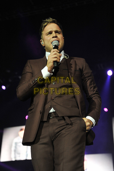 Olly Murs .performing live in concert at the o2 Arena, Greenwich, London, England, UK, 4th February 2012..music live on stage gig performing half length suit microphone brown singing hand in pocket .CAP/MAR.© Martin Harris/Capital Pictures.
