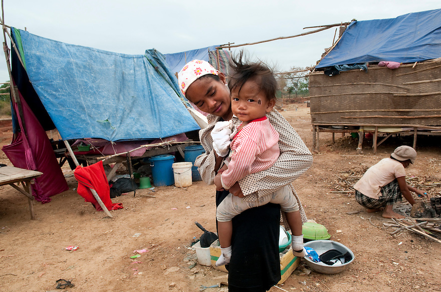 PHNOM PENH, CAMBODIA-- Sos Nhor holds her daughter, Yas Sopheap. Six families members are living under a makeshift tent at the base of Udon Mountain since December, 2009.  PHOTO BY JODI HILTON