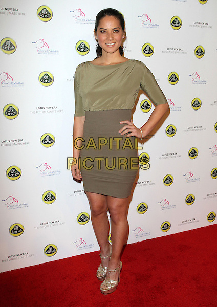 OLIVIA MUNN .U.S. Launch Event for New Lotus Carst held at A Private Residence, Los Angeles, CA, USA, .12th November 2010..full length  green silk satin khaki dress hand on hip gold platform sandals .CAP/ADM/KB.©Kevan Brooks/AdMedia/Capital Pictures.