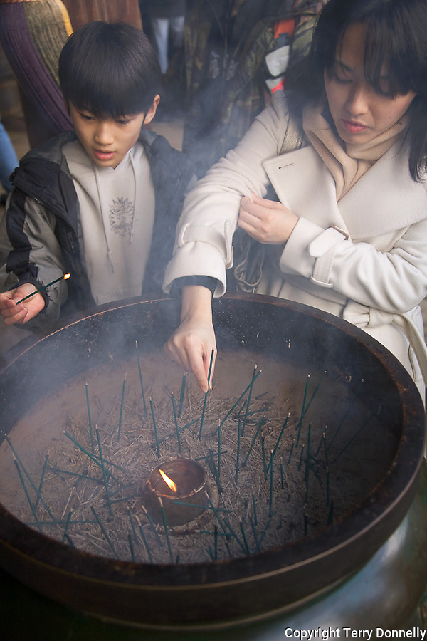 Kyoto City,  Japan<br /> Kiyomizu Temple, two young people burning incense in a large temple urn