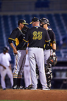 Bradenton Marauders pitching coach Jeff Johnson (23) talks with relief pitcher Miguel Rosario (38) and catcher Taylor Gushue (17) during a game against the Tampa Yankees on April 11, 2016 at George M. Steinbrenner Field in Tampa, Florida.  Tampa defeated Bradenton 5-2.  (Mike Janes/Four Seam Images)