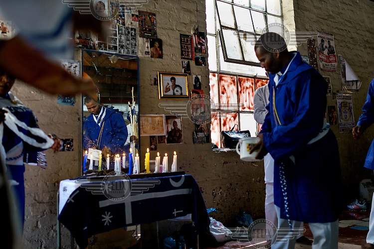 Members of the Zionist Church hold a service in the weight's room of George Khosi's Hillbrow Boxing Club. The church rents the space for a Sunday 'spirited prayer meeting'.  Hillbrow, in downtown Johannesburg, is the city's most notorious neighbourhood. It is overcrowded, ridden with illegal squats and suffers from high levels of crime much of which is related to the thriving illicit drug trade. Against this backdrop, George Khosi's story is not atypical. A childhood spent on the streets, where he survived by committing petty crime and hustling, led to imprisonment at the age of 16. Because he was big and looked older than his age this incarceration was in an adult institution. Here he began to fight since, as he says 'they wanted to make me a woman and I didn't want to be a woman.' When he got out, he took up boxing in earnest. His prospects as a professional boxer looked bright until he was shot and left for dead during a burglary. He lost his right eye and now walks with a limp. His boxing career seemed over but George picked up his gloves again, this time to teach Hillbrow's youngsters. His gym became a place of hope and discipline for local youth, keeping them of the streets and even producing some national champions.