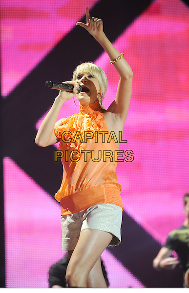 CARRIE UNDERWOOD .2008 CMA Music Festival Nightly Concert held on Vault Concert Stage at LP Field, Nashville, Tennessee, USA..June 6th, 2008.stage concert live gig performance music half length 3/4 orange top white shorts arm in air mouth open ruffled ruffles microphone singing funny face .CAP/ADM/LF.©Laura Farr/AdMedia/Capital Pictures.