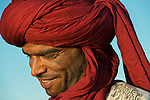 Portrait of a smiling Moroccan man with red turban.