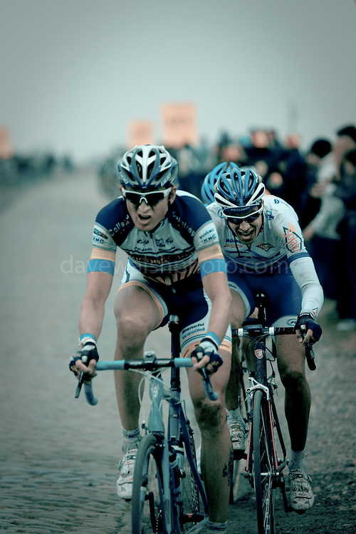 Swedish cyclist Gustav Larsson leads Jean-Lou Paiani on the pavé 13km from the finish of the 2012 Paris Roubaix professional cycling race classic. Here, the riders are passing Gruson, the 3rd last section of cobbles, 243km into the 256.5km route from Compiègne, near Paris, to Roubaix, northern France, which crosses 51.5km of pavé - 27 sections of ancient cobblestones, along the way. Larsson finished 31st, Paiani 30th.