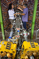 Italy. Lazio region. Frascati. Laboratori Nazionali di Frascati (LNF). Istituto Nazionale di Fisica Nucleare (INFN). Catalina Curceanu (L) and Florin Sighi (R), both romanian citizens and nuclear physicists, are talking near the Kloe detector (used for taking data) at the European Phi-factory Daphne (Daphne means Double Angular for Phi factory for Nice Experiment). Daphne is a particle accelerator in a circular collider, an Electron–Positron Collider for high precision elementary particle physics. The main objective of this project is to investigate problems on fundamental symmetries, electroweak and strong quantum chromodynamics (QCD) physics that may be explored and investigated by scientists. The INFN - the National Institute of Nuclear Physics - is an organization dedicated to the study of the fundamental constituents of matter, and conducts theoretical and experimental research in the fields of subnuclear, nuclear, and astroparticle physics. Fundamental research in these areas requires the use of cutting-edge technologies and instrumentation, which the INFN develops both in its own laboratories and in collaboration with the world of industry. Frascati is a town and comune in the province of Rome. It is located 20 kilometres south-east of Rome. Frascati is closely associated with science, being the location of several international scientific laboratories. Romanian immigration. 30.09.2011 © 2011 Didier Ruef