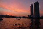 River traffic on the Chao Phraya at sunset in Bangkok, Thailand
