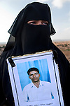 Khaltu Muhammad Kamushi holds a portrait of her brother Midoud Muhammad Kamushi, 53, during the burial of eight bodies found last week in a mass grave near the town of Al-Qala in the Nefusa Moutains, Libya, Friday, Sept. 30, 2011. The eight were reburied next to 35 bodies found in a separate mass grave in the area. Members of the Amazigh indigenous tribe, the men were arrested from their homes and at checkpoints by pro-Gaddafi forces, imprisoned, and finally executed sometime in June. The men, many of them related as fathers and sons, or as brothers, were missing until the first, larger mass grave was found in mid-August.
