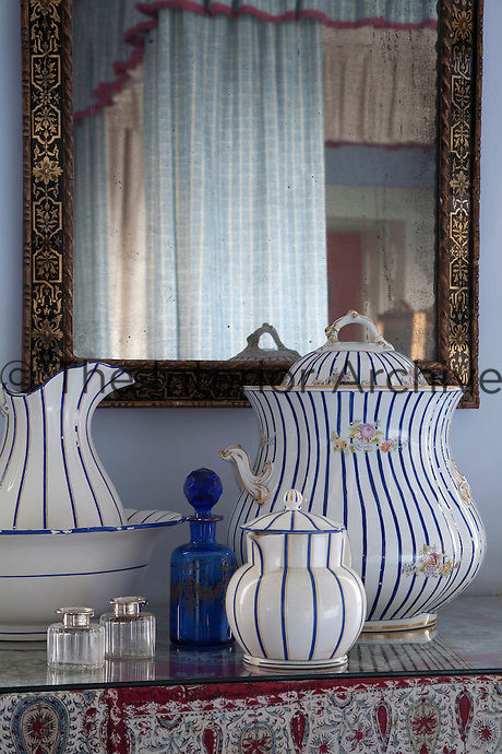 The blue bedroom is furnished with a four-poster bed and has a collection of blue and white porcelain on display
