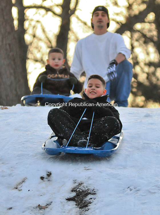 WATERBURY, CT 08 JANUARY 2013- 010813JS01-- Justin Perez, 9. of Waterbury, takes a sled down the hill at Hamilton Park in Waterbury on Tuesday as his step brother Jose Morales, 4, and family friend Curtiss Cykley of Middlebury, right, look on. Justin and Jose's father, Jose Morales, Sr.,  was stationed at the bottom of the hill to make sure the children did not hit any trees at the end of the run. .Jim Shannon Republican American