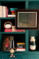 In the living room the painted wooden panelling and bookshelves are painted in a teal colour by the Paint and Paper Library. Ideal for displaying various objects in complimentary colours.