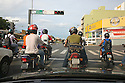 Motorcyclist stopping at traffic lights in the morning. Cuiaba, Mato Grosso, Brazil