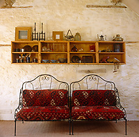 A pair of wrought-iron chairs with carpet seats beneath a length of open shelving on a whitewashed wall
