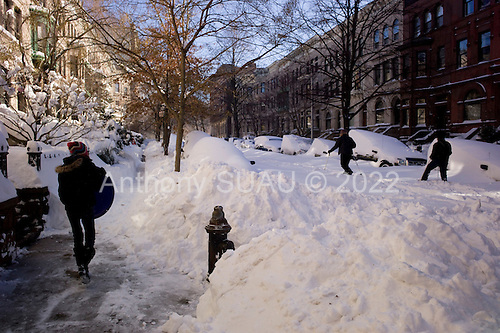 Brooklyn, New York<br /> December 27, 2010<br /> <br /> Snow blizzard on the East Coast. Oxanna Suau (10) makes her way up 4th Street towards 8th Avenue to the Park to sled as skiers move up the un-plowed street.