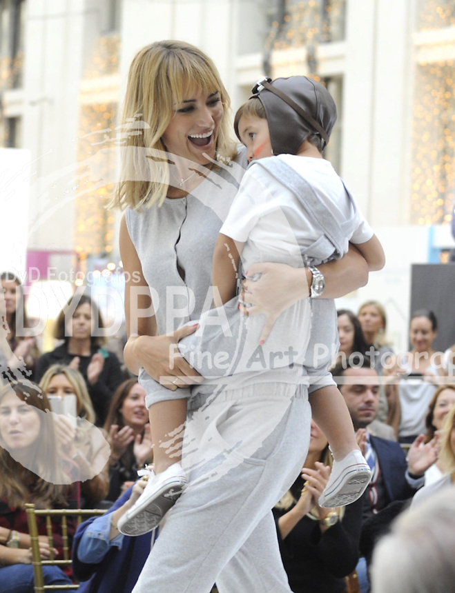 Fashion designer and model Alba Carrillo greets after show holds her son ( Former moto Gp rider Fonsi Nieto´s son)