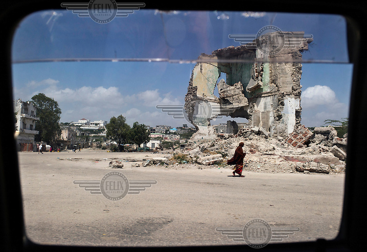 A view of a destroyed building, a result of 21 years of civil war, seen from the window of a vehicle.