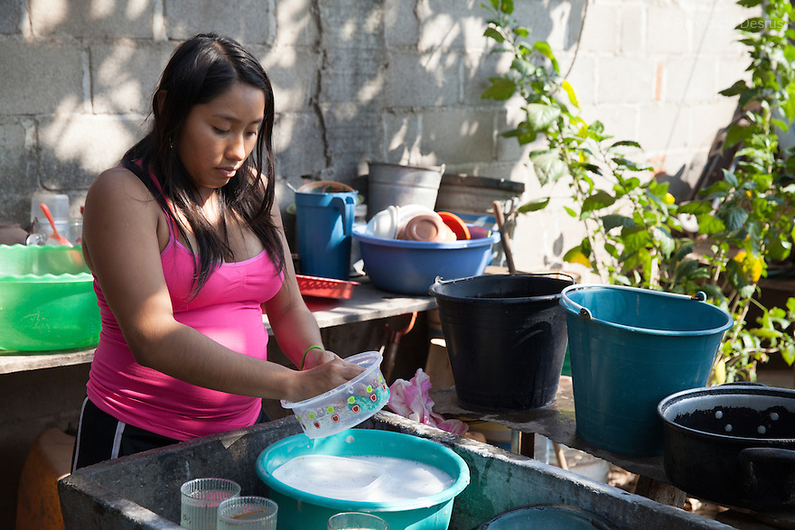 """María José Guerra Santiago washes dishes at her home in Juchitán, Mexico on February 17, 2016. María José, 17, proudly wears a wedding ring – she got married in January, and is five-months pregnant. She looks forward to the respect she says being a married woman – aseñora- and having a baby will bring her in the eyes of others. Unlike her husband, she used to love going dancing but now she lives with her in-laws in Juchitán in the southern Mexican state of Oaxaca. """"I won't be able to play like I did before,"""" she laments. While Mexico has outlawed marriage under the age of 18, many young girls become unofficial wives and mothers much earlier. In Juchitán, teenage pregnancy is expected, even prized. Mexico ranks first in teenage pregnancies among the member countries of the Organization for Economic Co-operation and Development(OECD). Photo by Bénédicte Desrus"""