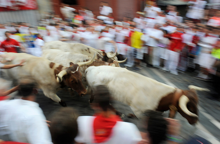 Participants run ahead the leading oxes during the third San Fermin Festival´s running of the bulls, on July 9, 2013, in Pamplona, Basque Country. A leading ox has dead into the bullring during the third running of the bulls. On each day of the eight San Fermin festival days six bulls are released at 8:00 a.m. (0600 GMT) to run from their corral through the narrow, cobbled streets of the old navarre town over an 850-meter (yard) course. Ahead of them are the runners, who try to stay close to the bulls without falling over or being gored. (Ander Gillenea / Bostok Photo)