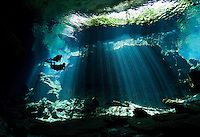 RX0638-D. scuba divers (model released) swim into a curtain of light shining down through the opening to a cenote, the entranceway to caverns and tunnels waiting to be explored. Riviera Maya, Yucatan Peninsula, Mexico.<br /> Photo Copyright &copy; Brandon Cole. All rights reserved worldwide.  www.brandoncole.com