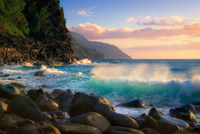 Soft sunset light reflects off the ocean shore looking towards the Na Pali Coast, Hawai'i.