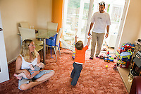 A woman sitting crossed-legged at home on her living room carpet, breastfeeding her baby, whilst her husband plays with their older boy.<br /> <br /> 09/07/2011<br /> Hampshire, England, UK