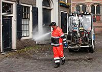 Medewerker van de reinigingsdienst Amsterdam, spuit de straat schoon