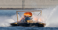 Flames come from the engine compartment as the The Plumbing Driver Kevin Aylesworth drives his burning boat around the course preparing to eject from his boat during the Hydroplane Race Heat 2B after his boat caught on fire during the race on Lake Washington in Seattle on Sunday Aug. 6, 2006. (AP Photo/Kevin P. Casey)