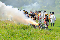 British artillery unit, in blue coats with red facings, fires field cannon during a Revolutionary War re-enactment at Fort Ticonderoga, New York, USA.