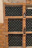 Wine bottles in square bins in the wine cellar. Matusko Winery. Potmje village, Dingac wine region, Peljesac peninsula. Matusko Winery. Dingac village and region. Peljesac peninsula. Dalmatian Coast, Croatia, Europe.