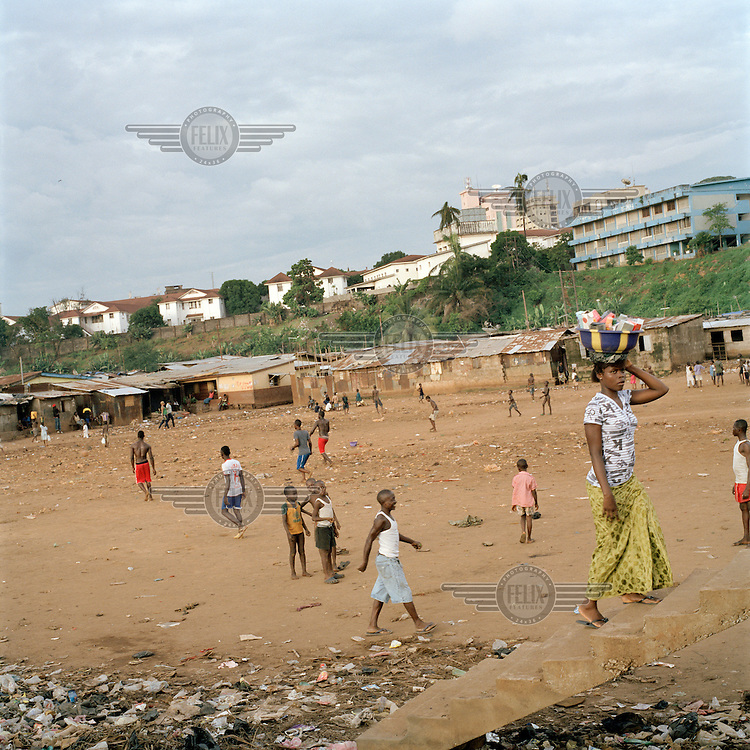 Young people and children on the  football pitch in Kroo Bay, the centre of the slum which is collectively protected from being built on as it is the only open space where children can play. Kroo Bay, a slum built on a rubbish dump on the eastern outskirts of the capital Freetown, houses around 6,500 people. The rubbish that is washed down the hill from the city toward Kroo Bay is compacted in the bay to the extent that houses can be built on the surface, thus reclaiming land from the sea. .