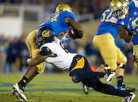 Michael Barton of California tackles Paul Perkins of UCLA during the game at Rose Bowl in Pasadena, California on October 12th, 2013.   UCLA defeated California, 37-10.