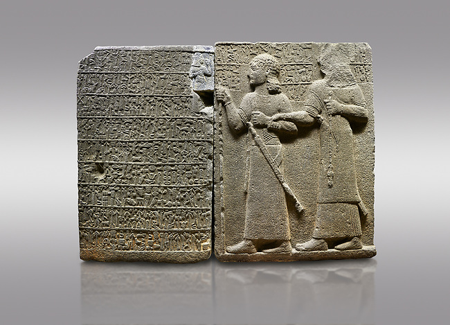 """Picture & image of Hittite monumental relief sculpted orthostat stone panel of Royal Buttress. Basalt, Karkamıs, (Kargamıs), Carchemish (Karkemish), 900-700 B.C. Anatolian Civilisations Museum, Ankara, Turkey.<br /> <br /> Hieroglyph panel (left) - Discourse of Yariris. Yariris presents his predecessor, the eldest son Kamanis, to his people. <br /> Right Panel - King Araras holds his son Kamanis from the wrist. King carries a sceptre in his hand and a sword at his waist while the prince leans on a stick and carries a sword on his shoulder. <br /> <br /> Hieroglyphs reads; """"This is Kamanis and his siblings.) held his hand and despite the fact that he is a child, I located him on the temple. This is Yariris' image"""".<br /> <br /> Against a gray background."""