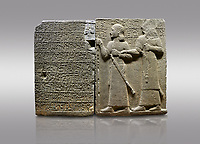 Picture &amp; image of Hittite monumental relief sculpted orthostat stone panel of Royal Buttress. Basalt, Karkamıs, (Kargamıs), Carchemish (Karkemish), 900-700 B.C. Anatolian Civilisations Museum, Ankara, Turkey.<br /> <br /> Hieroglyph panel (left) - Discourse of Yariris. Yariris presents his predecessor, the eldest son Kamanis, to his people. <br /> Right Panel - King Araras holds his son Kamanis from the wrist. King carries a sceptre in his hand and a sword at his waist while the prince leans on a stick and carries a sword on his shoulder. <br /> <br /> Hieroglyphs reads; &quot;This is Kamanis and his siblings.) held his hand and despite the fact that he is a child, I located him on the temple. This is Yariris' image&quot;.<br /> <br /> Against a gray background.
