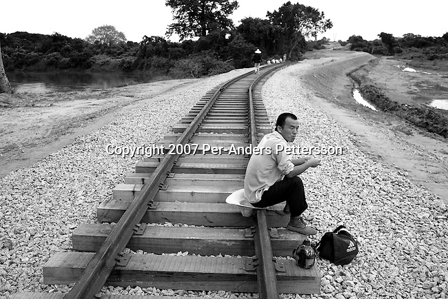 DONDO, ANGOLA APRIL 4: An unidentified Chinese railway worker sits on the newly put tracks on April 4, 2007 in Dondo, about 200 kilometers outside Luanda, Angola. Chinese companies are building and upgrading two different railways in Angola, and this part is about 500 kilometers long. All the special equipment has been shipped from China and hundreds of workers live in military style road camps. They are moved as the tracks are laid down. Tens of thousands of Chinese has come to Africa the last years to work in infrastructure projects and businesses. Chinese companies are often the lowest bidders for contracts, pricing out the more expensive European companies. The Chinese people often live where they work and rarely interact with the local population. Most Chinese don't speak English and they are mostly staying in the compounds cooking their Chinese food. (Photo by Per-Anders Pettersson)..