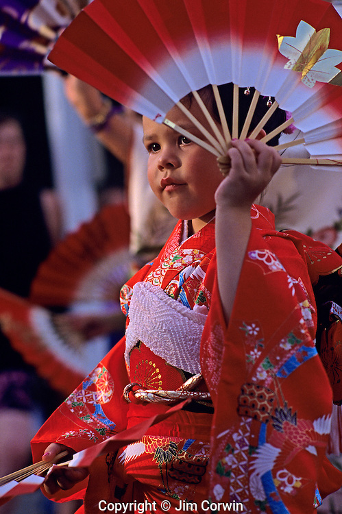 Young girl dancing with fan at the Bon Odori celebration Seattle Washington State USA