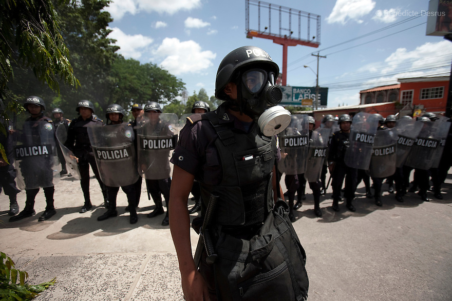 4 July 2009 - Tegucigalpa, Honduras  Police and soldiers stand guard as thousands of supporters of Honduras' ousted President Manuel Zelaya protest in Tegucigalpa, capital of Honduras. Zelaya has been forced into exile after being arrested by a group of soldiers in an apparent military coup. Zelaya was warned he would be arrested if he return to Honduras but has vowed to return to Honduras on Sunday accompanied by Latin American leaders. Photo credit: Benedicte Desrus