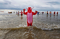 Pictured: A man dressed as a red minster in the sea. Tuesday 26 December 2017<br /> Re: Hundreds took part in this year's Boxing Day Walrus Dip which see people in fancy dress taking to the sea at Cefn Sidan beach in Pembrey Country Park, west Wales, UK.