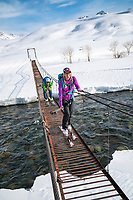 Skiers crossing a bridge over a river while ski touring in the Suusamyr region of Kyrgyzstan. The man is playfully pretending to tuck on the bridge, with his skis still on.
