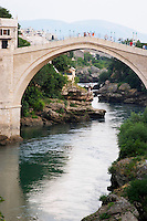 View along the river of the old reconstructed bridge. Historic town of Mostar. Federation Bosne i Hercegovine. Bosnia Herzegovina, Europe.
