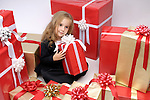 Little girl sitting surrounded by a huge pile of Christmas gift boxes