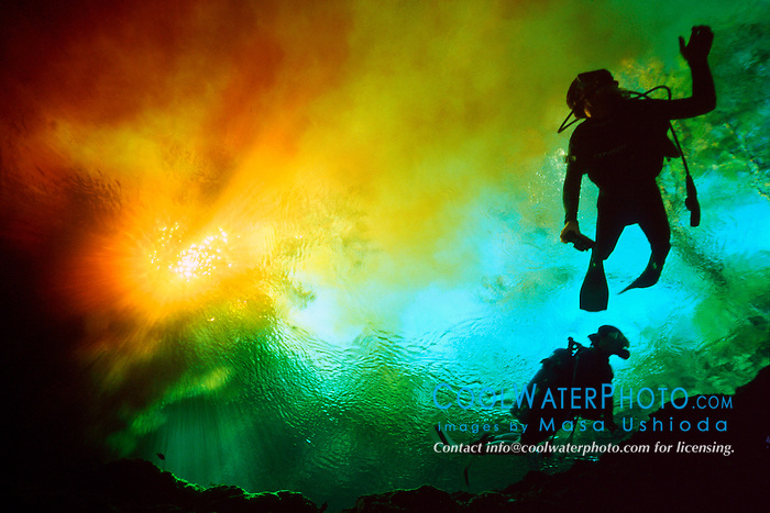 scuba divers at cross section of blackish .water from Santa Fe River and clear water .from Devils Ear Spring, Ginnie Springs, .High Springs, Florida.