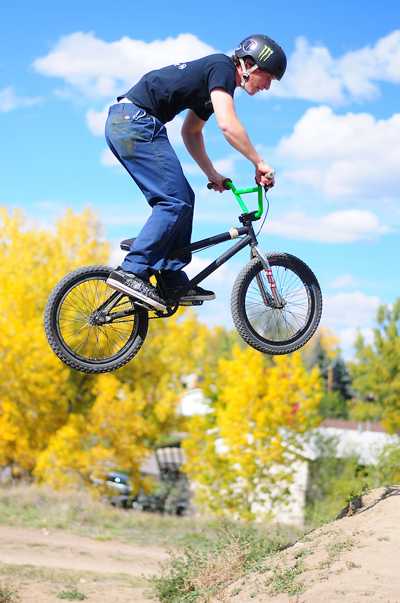 """A mountain biker bmx dirt jumping at the """"Sunset trails"""" in Lakewood, Colorado on October 19, 2008. sunset trails"""