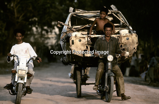 A father and son transport an old car on a carriage on March 11, 1998 in central Phnom Penh, Cambodia. Cambodia is one of the poorest countries in the world. From 1975-1979 about 1,7 million people were killed (about 21 percent of the population), in one of the worst human tragedies during recent history. It was led by Pol Pot, who used extremist ideology to repress and murder on a massive scale. (Photo by: Per-Anders Pettersson)